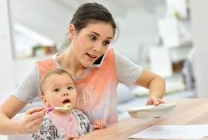 Mother feeding child while talking on phone